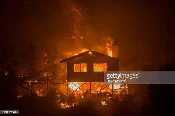 A structure burns at the Lilac Fire in the early morning hours of December 8 2017 near Bonsall California Strong Santa Ana winds are pushing multiple...