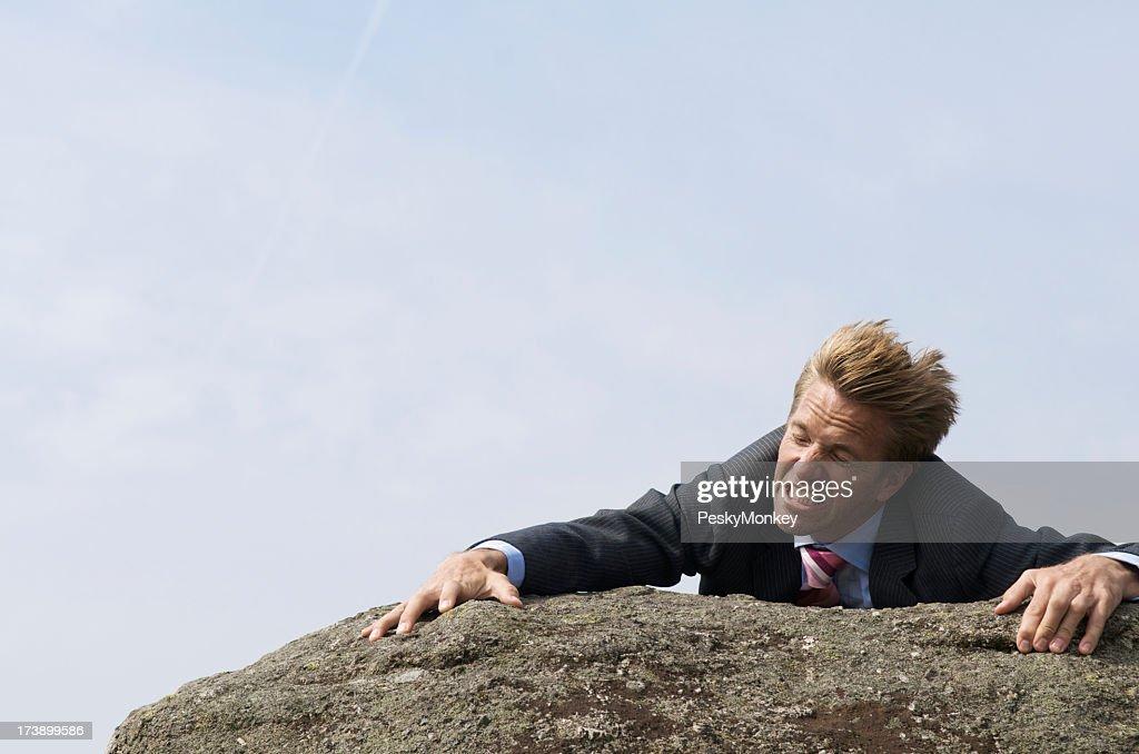 Struggling Businessman Clinging to Edge of Windblown Rock