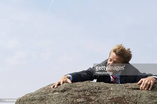 Struggling Businessman Clinging to Edge of Windblown Rock