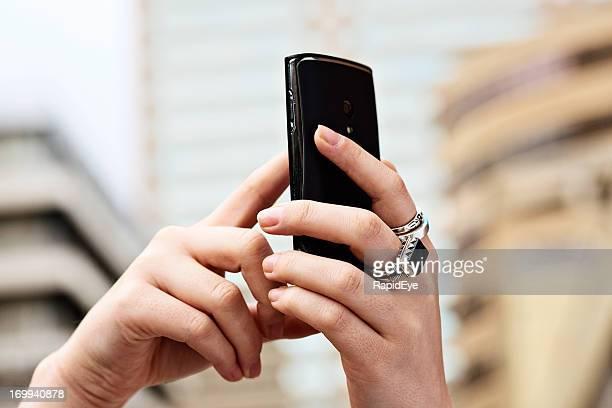 Struggling for a signal, female hands hold mobile phone aloft