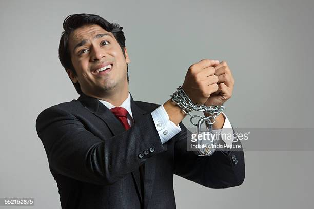 Struggling young businessmans hand tied in chain over gray background