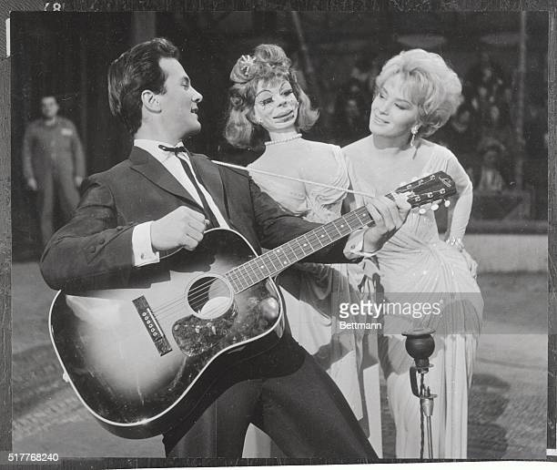 Strumming his trusty guitar singeractor pat Boone serenades a buxom dummy named Godiva in a scene for the seven parts Production of The Main...