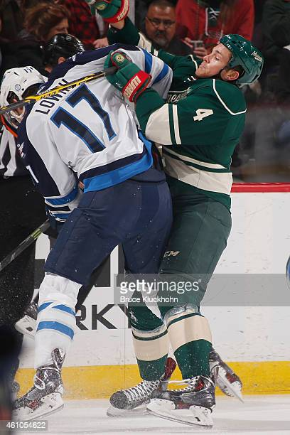 Stu Bickel of the Minnesota Wild and Adam Lowry of the Winnipeg Jets battle for the puck during the game on December 27 2014 at the Xcel Energy...