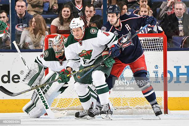 Stu Bickel of the Minnesota Wild and Jared Boll of the Columbus Blue Jackets battle for position in front of goaltender Darcy Kuemper of the...