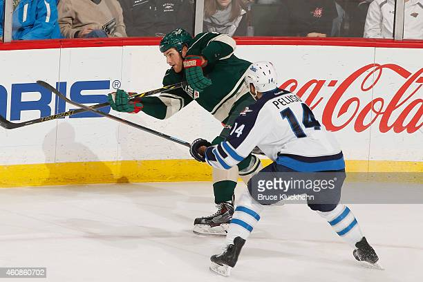 Stu Bickel of the Minnesota Wild clears the puck with Anthony Peluso of the Winnipeg Jets defending during the game on December 27 2014 at the Xcel...