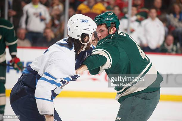 Stu Bickel of the Minnesota Wild fights with Chris Thorburn of the Winnipeg Jets during the game on December 27 2014 at the Xcel Energy Center in St...
