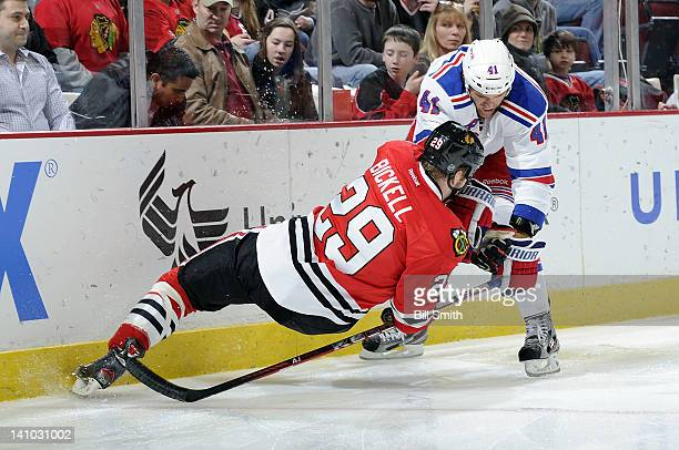 Stu Bickel of the New York Rangers and Bryan Bickell of the Chicago Blackhawks get tangled as they try to grab the puck during the NHL game on March...