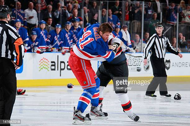 Stu Bickel of the New York Rangers fights against Ryan Carter of the New Jersey Devils at the start of the first period at Madison Square Garden on...