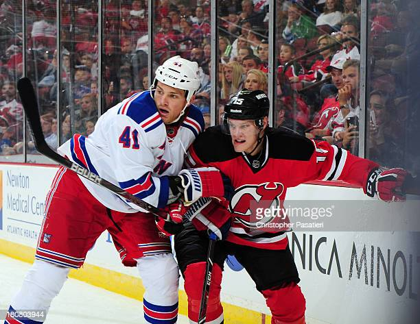 Stu Bickel of the New York Rangers grabs Harri Pesonen of the New Jersey Devils during the third period of a preseason game on September 16 2013 at...