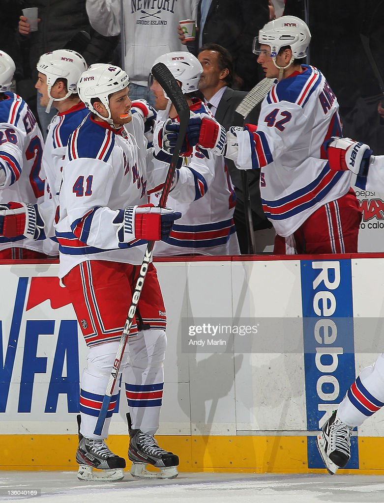 Stu Bickel #41 of the New York Rangers is congratulated by his teammates after getting his first NHL point, an assist, during the game against the New Jersey Devils at the Prudential Center on December 20, 2011 in Newark, New Jersey.