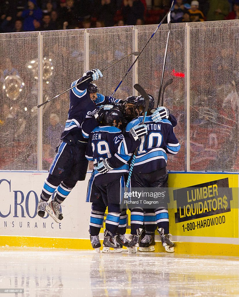 Stu Higgins #22 of the Maine Black Bears jumps on his teammates Ben Hutton #10 and Connor Leen #29 after a Maine goal during NCAA hockey action against the Boston University Terriers in the 'Citi Frozen Fenway 2014' at Fenway Park on January 11, 2014 in Boston, Massachusetts.