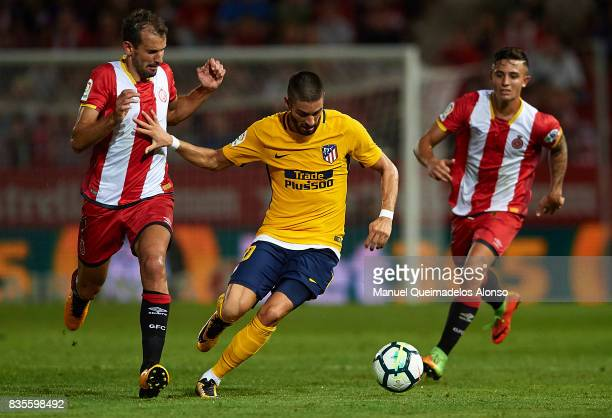 Stuani of Girona competes for the ball with Yannick Carrasco of Atletico de Madrid during the La Liga match between Girona and Atletico de Madrid at...