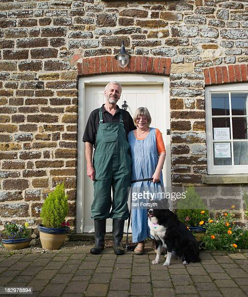 Stuart and Elizabeth Smith pose with their dog 'Beth' outside their cottage before work begins at the start of the first grape harvest this year at...