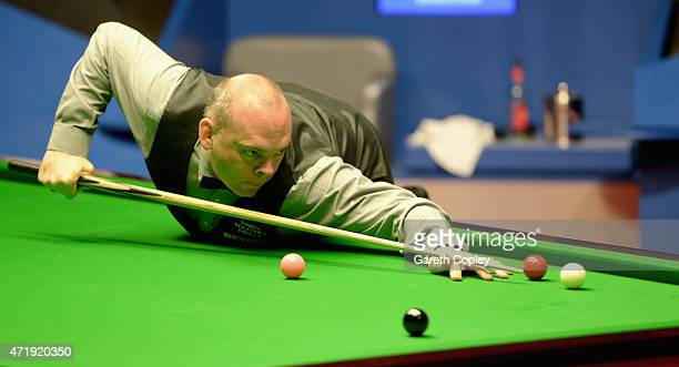 Stuart Bingham plays a shot against Judd Trump during their semi final on day fifteen of the 2015 Betfred World Snooker Championship at Crucible...