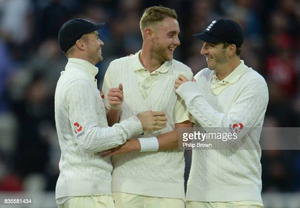 Stuart Broad of England celebrates with James Anderson and Toby RolandJones after dismissing Jason Holder of the West Indies during the third day of...