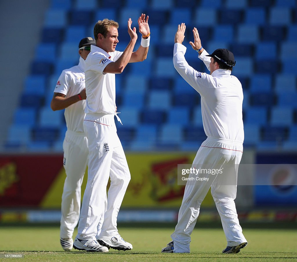 Stuart Broad of England celebrates with teammate Eoin Morgan after dismissing Umar Gul of Pakistan during the first Test match between Pakistan and England at The Dubai International Cricket Stadium on January 19, 2012 in Dubai, United Arab Emirates.