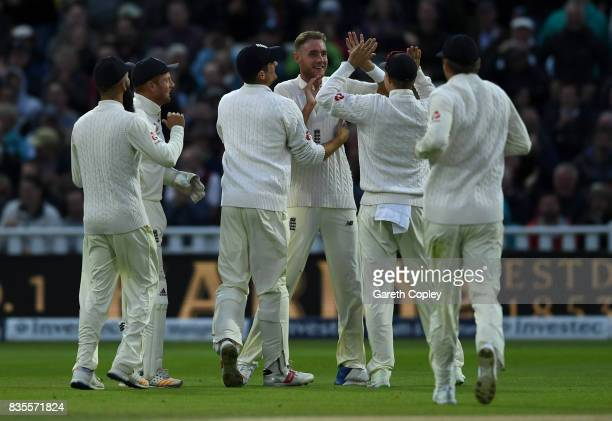 Stuart Broad of England celebrates with teammates after dismissing West Indies captain Jason Holder during day three of the 1st Investec Test between...
