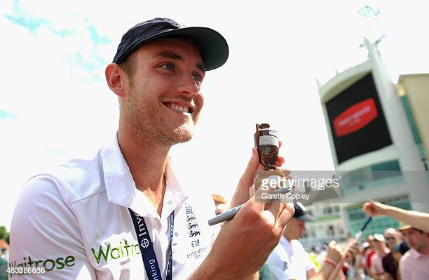 Stuart Broad of England is handed a replica ashes urn to sign after winning the 4th Investec Ashes Test match between England and Australia at Trent...