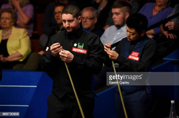 Stuart Carrington lines up a shot against Liang Wenbo during their first round match of the World Snooker Championship at Crucible Theatre on April...