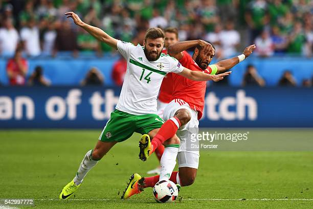 Stuart Dallas of Northern Ireland and Ashley Williams of Wales compete for the ball during the UEFA EURO 2016 round of 16 match between Wales and...