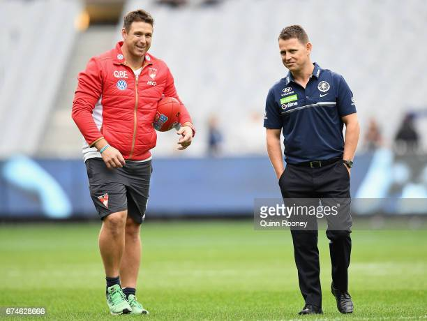 Stuart Dew the assistant coach of the Swans speaks to Blues head coach Brendon Bolton during the round six AFL match between the Carlton Blues and...