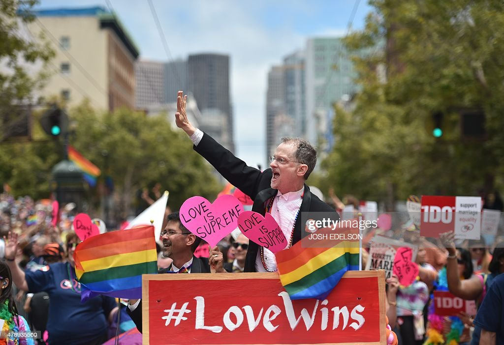 Stuart Gaffney (L) and John Lewis (C), plaintiffs in the 2008 Defense of Marriage Act (DOMA) case, celebrate while traveling along Market Street during the annual Gay Pride Parade in San Francisco, California on June 28, 2015, two days after the US Supreme Court's landmark ruling legalizing same-sex marriage nationwide.