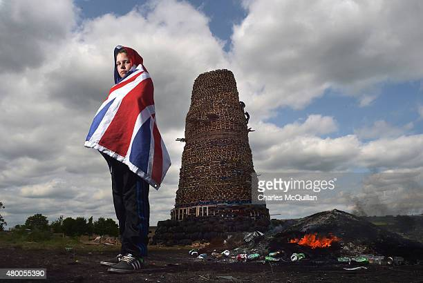 Stuart Gillanders stands guard over a large bonfire construct in preparation for the 11th night bonfire at the New Mossley estate on July 9 2015 in...