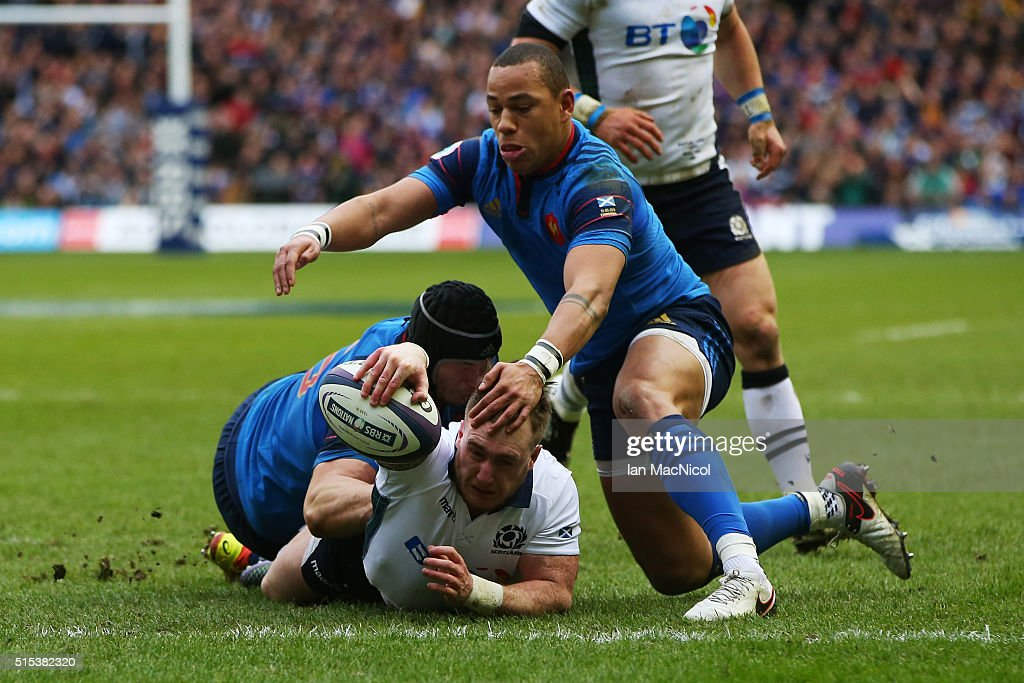 Stuart Hogg of Scotland dives through the tackles from Yacouba Camara and Gael Fickou of France to score his team's opening try during the RBS Six Nations match between Scotland and France at Murrayfield Stadium on March 13, 2016 in Edinburgh, Scotland.