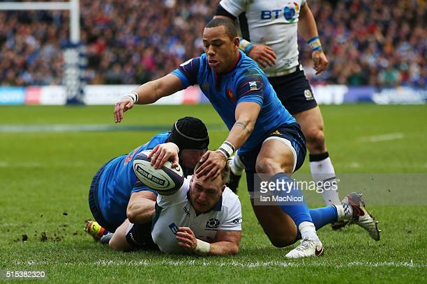 Stuart Hogg of Scotland dives through the tackles from Yacouba Camara and Gael Fickou of France to score his team's opening try during the RBS Six...