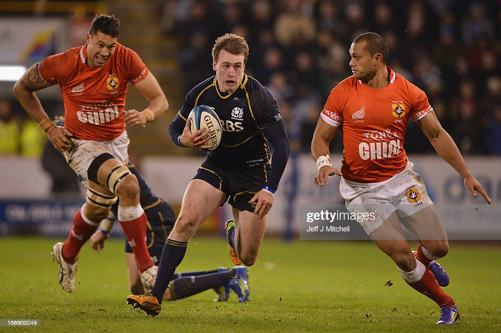 Stuart Hogg of Scotland goes past Joe Tu'ineau and Alipate Fatafehi of Tonga during the international match between Scotland and Tonga at Pittodrie stadium on November 24, 2012 in Aberdeen,Scotland.