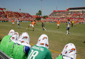 Stuart Holden of the Houston Dynamo kicks the ball away from Kansas City Wizards defenders as the substitutes sit with wet Gatorade towels on their...