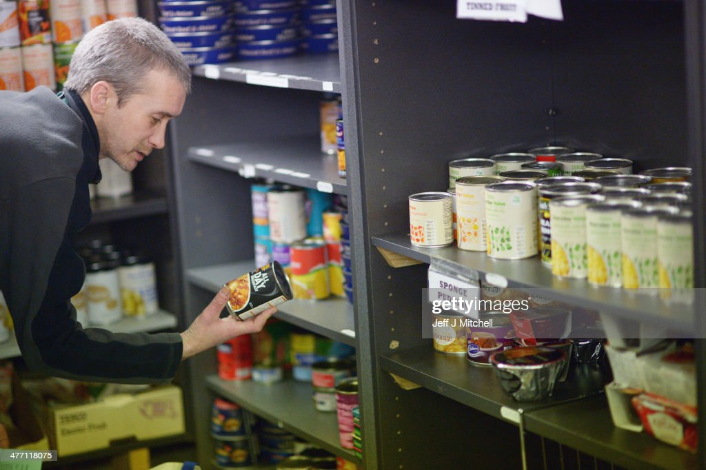 A Stuart Little volunteer holds a can as he packs food at a food bank on March 7, 2014 in Whitburn, Scotland. Charities based in Scotland are reporting that many families are living in poverty having to turn to food banks, and are struggling to heat their homes and clothe their children and themselves. The Trussell trust runs a network of foodbanks throughout the UK, giving emergency food to people in crisis. In the past year demand has risen in Scotland and the rest of the UK.