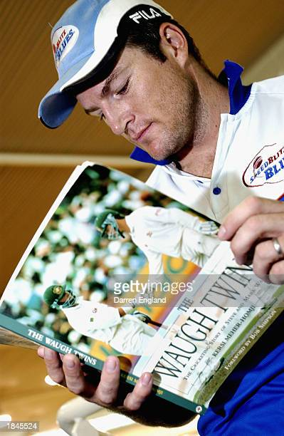 Stuart MacGill of New South Wales takes a break to read a book during a training session at Brisbane Grammar School in preparation for the Pura Cup...