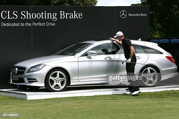 Stuart Manley of Wales pats a Mercedes Benz car making a holeinone on the 3rd tee during day three of the World Cup of Golf at Royal Melbourne Golf...