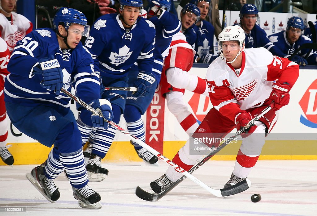 Stuart Percy #50 of the Toronto Maple Leafs gets the puck away from Mikael Samuelsson #37 of the Detroit Red Wings during NHL Preseason action at the Air Canada Centre September 28, 2013 in Toronto, Ontario, Canada.