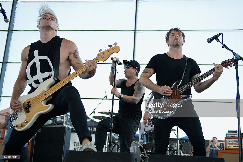 Stuart Richardson, Ian Watkins and <a gi-track='captionPersonalityLinkClicked' href=/galleries/search?phrase=Mike+Lewis&family=editorial&specificpeople=763025 ng-click='$event.stopPropagation()'>Mike Lewis</a> of Lostprophets perform on stage during Warped Tour at Marcus Amphitheatre on August 1, 2012 in Milwaukee, United States.