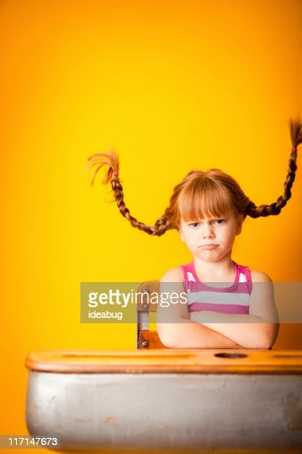 Stubborn Red-Haired Girl with Arms Crossed in School Desk : Stock Photo