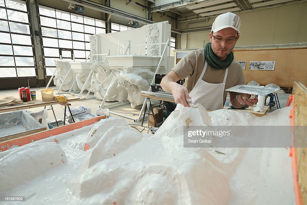 Stucco master Andre Ermicher fortifies the underside of a silicon mould with plaster at the Schlossbauhuette studio where a team of sculptors is creating decorative elements for the facade of the Berliner Schloss city palace on February 12, 2013 in Berlin, Germany. The Berliner Schloss was the residence of the Prussian Kaiser and was among the major architectural landmarks of Berlin until it was heavily damaged by Allied bombing in 1945. The communist authorities of East Berlin demolished the building in the 1950s, and today's Berlin government is pursuing an ambitious project to rebuild the palace according to a design by Italian architect Franco Stella, which will recreate the facade of the building but with a modern interior at a cost of approximately EUR 590 million. The Humboldt Forum, the foundation leading the project, has given the Schlossbauhuette sculptors the formidable task of recreating the hundreds of architectural elements that decorated the facade, and though some original pieces were saved, more often the sculptors have only old black and white photos as reference.