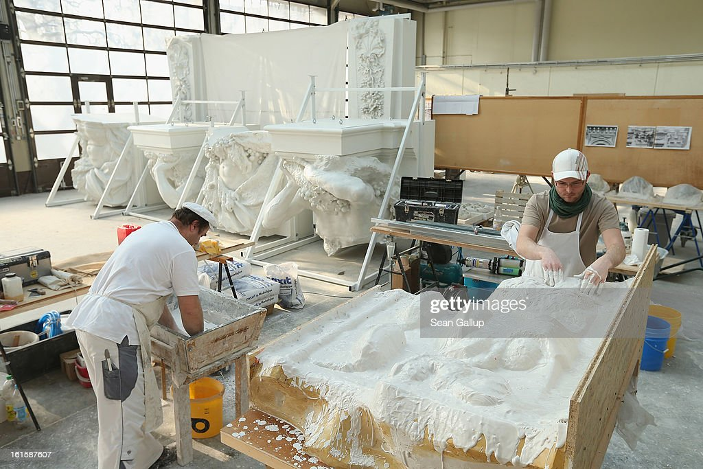 Stucco masters Christian Ortlepp (L) and Andre Ermicher fortify the underside of a silicon mould with plaster at the Schlossbauhuette studio where a team of sculptors is creating decorative elements for the facade of the Berliner Schloss city palace on February 12, 2013 in Berlin, Germany. The Berliner Schloss was the residence of the Prussian Kaiser and was among the major architectural landmarks of Berlin until it was heavily damaged by Allied bombing in 1945. The communist authorities of East Berlin demolished the building in the 1950s, and today's Berlin government is pursuing an ambitious project to rebuild the palace according to a design by Italian architect Franco Stella, which will recreate the facade of the building but with a modern interior at a cost of approximately EUR 590 million. The Humboldt Forum, the foundation leading the project, has given the Schlossbauhuette sculptors the formidable task of recreating the hundreds of architectural elements that decorated the facade, and though some original pieces were saved, more often the sculptors have only old black and white photos as reference.