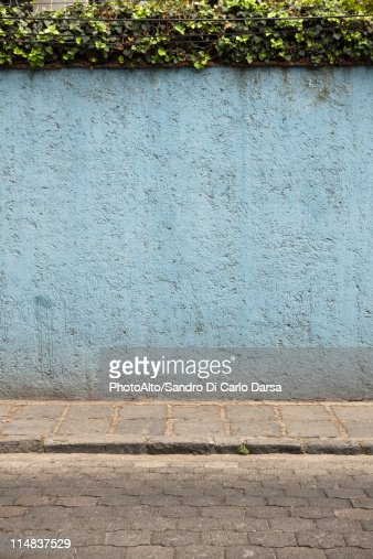 Stucco wall along cobblestone street