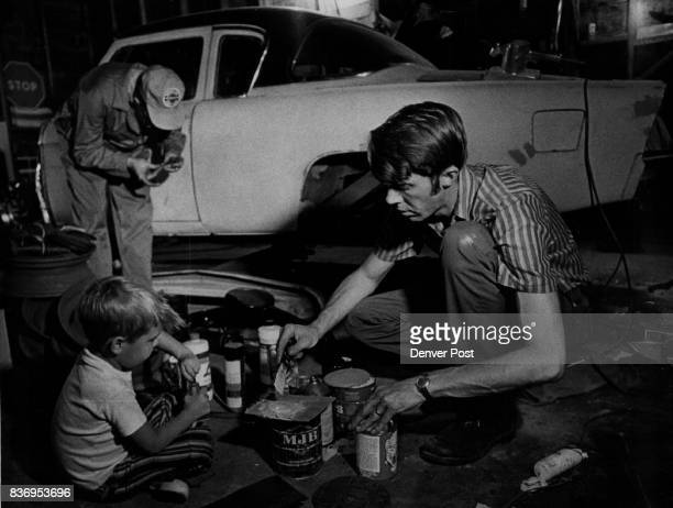 Studebaker Jim Smith gets help mixing body putty from his son Eric Smith age 4 Carl Farmer in background ***** car will be given to museum Eric Smith...