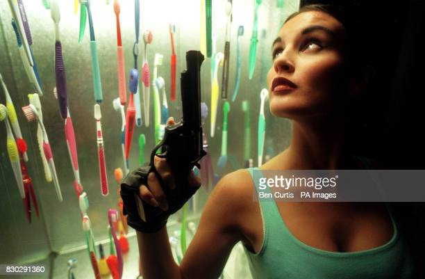 Student and model Michelle Watson dressed as computer games character Lara Croft is pictured next to a collection of hightech toothbrushes at a...