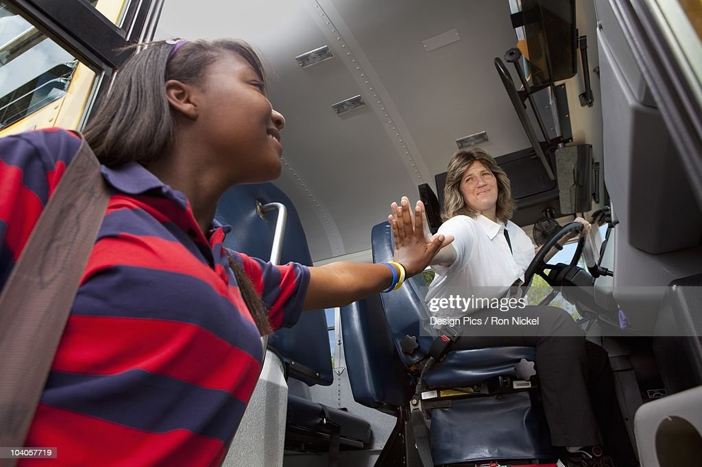 Student And School Bus Driver Slapping Hands In A 'high Five'