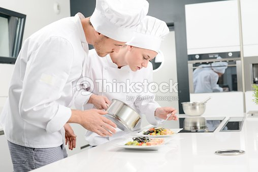 student and teacher in professional cook school kitchen preparing