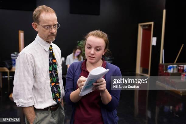 Student and teacher reading script in high school drama class