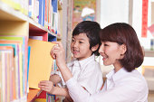 Student and Teacher Taking Book from a Bookshelf