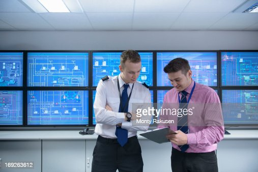 Student and tutor looking at clipboard in ship's engine room simulator : Stock Photo