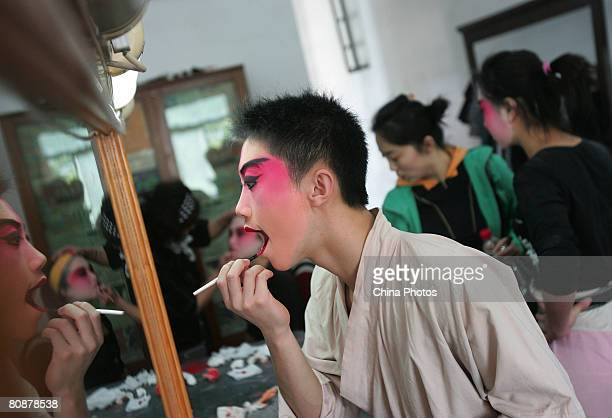 A student applies makeup before performing in a Peking Opera at the Affiliated Middle School of National Academy of Chinese Theatre Arts on April 26...