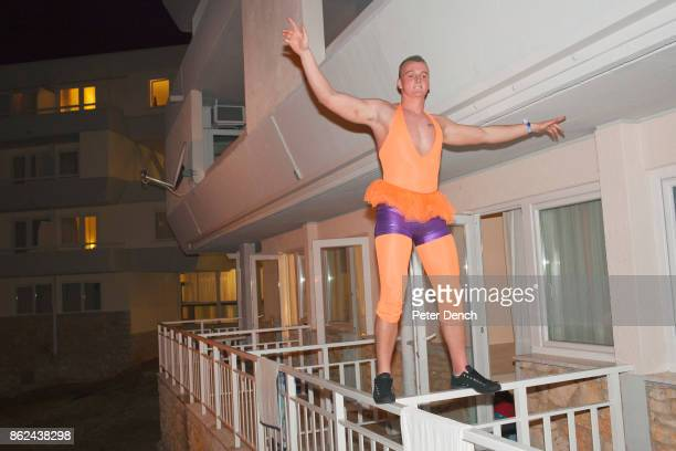 A student at Bangor University balances on a balcony dressed for the 'tight and bright' night out He is one of around a 1000 British university...