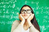 Pensive student on background of blackboard